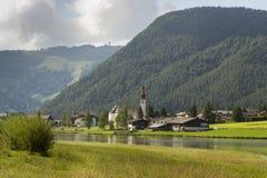 Sankt Ulrich am Pillersee with Jakobskreuz on the Buchensteinwand summit. In Kitzbuhel Alps Stock Photography