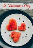Sankt valentin \ 's-dagvykort, vattenmelonhjärtaform på plattan, träbakgrund Top beskådar fotografering för bildbyråer