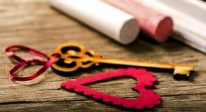 Sankt valentingarnering: hjärta och tangent, svart bräde och krita arkivbild