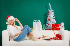 Sankt-Weihnachtsfrau, die auf Sofa sich entspannt Lizenzfreies Stockbild