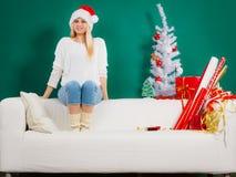 Sankt-Weihnachtsfrau, die auf Sofa sich entspannt Lizenzfreie Stockfotografie