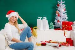 Sankt-Weihnachtsfrau, die auf Sofa sich entspannt Lizenzfreie Stockbilder