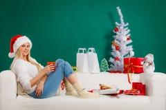 Sankt-Weihnachtsfrau, die auf Sofa sich entspannt Stockfotografie