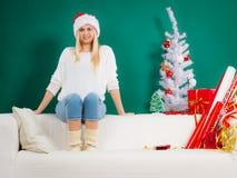 Sankt-Weihnachtsfrau, die auf Sofa sich entspannt Lizenzfreies Stockfoto