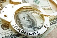 Sanktionen auf Handschellen und amerikanische Dollarscheine Wirtschaftliche Beschränkungen Stockbild