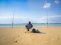 SANLUCAR DE BARRAMEDA, SPAIN - APRIL 12, 2015 - Situated at the. SANLUCAR DE BARRAMEDA, SPAIN - APRIL 12, 2015 - Fisherman fishing on an empty beach. Situated at Royalty Free Stock Photo