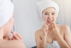 Sano blanco de la seda dental del uso de la mujer con el espejo en cuarto de baño foto de archivo libre de regalías