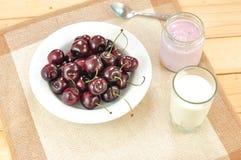 Sano del desayuno componga de una placa de la cereza, de un vidrio de leche y de un tarro de yogur en el paño con el fondo de mad imagenes de archivo