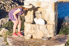 Sans-abri blanc et femme de chat jouant avec lui le concept de aide extérieur de mode de vie et d'amitié Photographie stock libre de droits