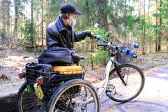 Sans-abri dans un fauteuil roulant allant sur un chemin forestier Le fauteuil roulant ? trois roues est ?quip? d'une bo?te pour d photographie stock libre de droits