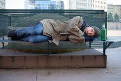 Sans-abri dormant sur le banc dans le froid Photo libre de droits