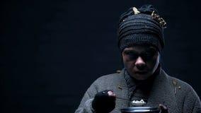 Sans-abri effray? avec le visage meurtri mangeant l'ort sur le fond noir, violence photo libre de droits