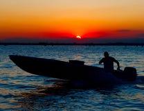 Sanset a Venezia. Imbarcazione a motore e siluetta umana Fotografia Stock