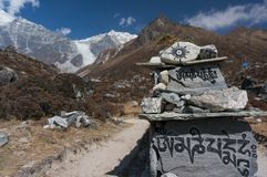Sanskrit mantra rock carving leading Langtang Lirung. Sanskrit mantra rock carving. Stones with buddhist mantra om mani padme hum in the Himalayan Mountains stock image