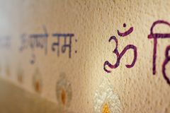 Sanskrit writing with om, aum, ohm symbol on the wall royalty free stock photo