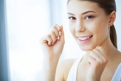 Santé et beauté La belle jeune fille avec les dents blanches nettoie Photo stock