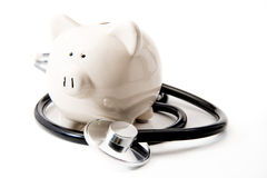 Santé financière - stéthoscope noir et tirelire image libre de droits