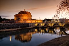 Sant` Angelo Castle and Tiber River in Rome, Italy by night. The Mausoleum of Hadrian, usually known as Castel Sant Angelo is a towering cylindrical building Royalty Free Stock Photos