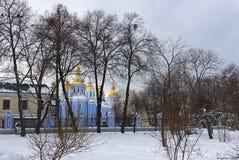 Sant Mishael a catedral dourado-abobadada, estando atrás das árvores do parque no inverno em Kiev fotografia de stock