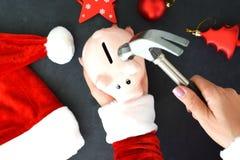 Santa's帮手为在圣诞节时间的高费用做准备,与存钱罐和锤子在圣诞节背景 免版税库存图片