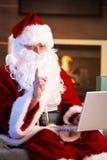 Santa à l'aide de l'ordinateur Photographie stock