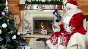 Santa à l'aide du comprimé, noel de papa se reposant dans la chaise avec l'appareil électronique, pièce avec la cheminée banque de vidéos