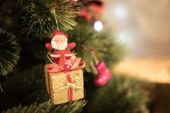 Santa& x27 καθίσματα κιβωτίων δώρων του s στο χριστουγεννιάτικο δέντρο στο νέο έτος Στοκ Εικόνα