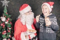 Santa και αστείο αγόρι με τα μπισκότα και γάλα στα Χριστούγεννα Στοκ φωτογραφία με δικαίωμα ελεύθερης χρήσης