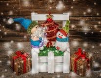 Santa και χιονάνθρωπος με δύο κιβώτια στο χωριό στο ξύλινο υπόβαθρο Στοκ Εικόνα