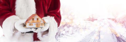 Santa με το σπίτι εκμετάλλευσης χειμερινών τοπίων Στοκ Εικόνες