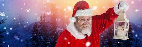 Santa με το φανάρι εκμετάλλευσης χειμερινών τοπίων Στοκ Φωτογραφίες