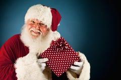 Santa: Να κρατήσει ψηλά το τυλιγμένο δώρο Χριστουγέννων στοκ εικόνα με δικαίωμα ελεύθερης χρήσης