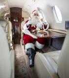 Santa που έχει τα μπισκότα και το αεριωθούμενο αεροπλάνο γάλακτος ιδιωτικά Στοκ φωτογραφίες με δικαίωμα ελεύθερης χρήσης