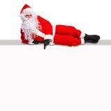 Santa που βρίσκεται σε ένα κενό σημάδι πινάκων διαφημίσεων στοκ εικόνα