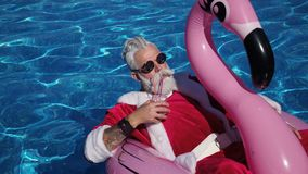 Santa που επιπλέει στο διογκώσιμο δαχτυλίδι στην πισίνα απόθεμα βίντεο