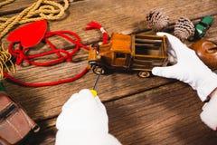 Santa που επισκευάζει το αυτοκίνητο παιχνιδιών κατά τη διάρκεια του χρόνου Χριστουγέννων Στοκ φωτογραφίες με δικαίωμα ελεύθερης χρήσης