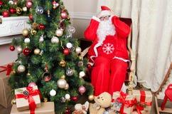 Santa στην πολυθρόνα κοντά στην εστία στοκ φωτογραφίες με δικαίωμα ελεύθερης χρήσης