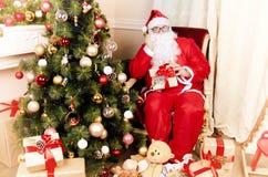 Santa στην πολυθρόνα κοντά στην εστία στοκ εικόνες