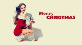 santa сексуальный Девушка красоты рождества нося красное платье держа подарки Стоковые Фотографии RF