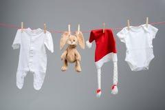 Ενδύματα μωρών και καπέλο santa σε μια σκοινί για άπλωμα Στοκ Εικόνες