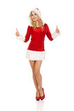 Женщина в одеждах santa показывать большие пальцы руки вверх Стоковое Фото