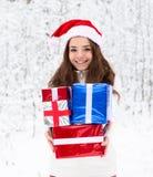 Κορίτσι εφήβων με το καπέλο santa και τα κόκκινα κιβώτια δώρων που στέκονται στο χειμερινό δάσος Στοκ Φωτογραφίες