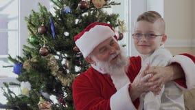 Santa abbraccia e schiaccia il ragazzo vicino all'abete archivi video