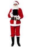 Santa affichant le PC neuf lancé de tablette Photo libre de droits