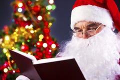 Santa affichant un livre Photographie stock