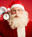 Santa with alarm clock. Happy Santa with alarm clock showing five minutes to midnight stock photography