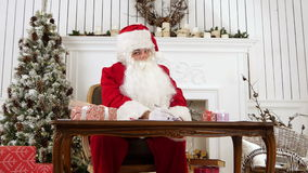 Santa answering letters in his workshop and explaining what it`s like to be Santa stock video