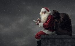 Santa apportant des cadeaux le réveillon de Noël Images libres de droits