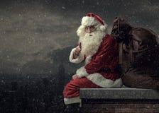 Santa apportant des cadeaux le réveillon de Noël Photographie stock libre de droits