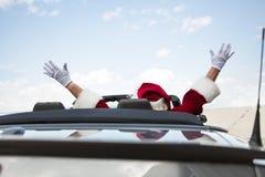 Santa With Arms Raised In cabriolet mot himmel arkivfoto